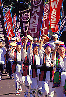 Several Okinawan women with purple head scarves and traditional ikat vests march in the Okinawan Festival Parade with tambourines held up in the air.