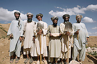 A group of labourers stand with their tools.