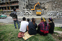 Local Tibetans watch as heavy machinery tears down the side of a mountain to make way for new homes and developments.  South-east Tibetan Plateau, in Sichuan Province, western China.