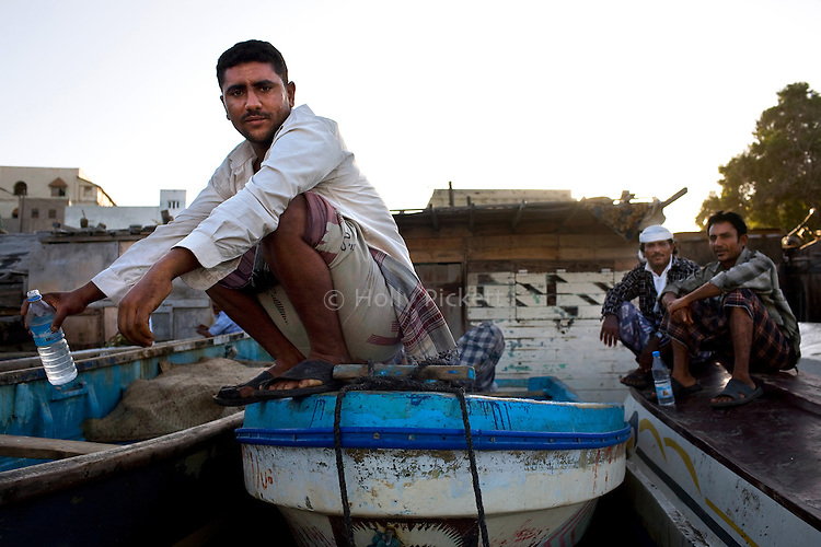 A fisherman perches atop a fishing boat near the fishmarket at dusk in Aden, Yemen, Dec. 2, 2009. A raging conflict with Houthi rebels in Yemen's north and clashes with separatists in the South continue to erode stability in the Arabian Peninsula's poorest state, where half of the population lives in abject poverty.