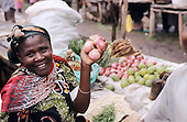Lolgorian, Kenya. Smiling woman selling onions and other produce at the market.
