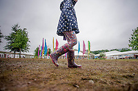 Thursday  29 May 2014, Hay on Wye, UK<br /> Pictured: A girl in brightly coloured boots walks along the muddy festival field at Hay <br /> Re: The Hay Festival, Hay on Wye, Powys, Wales UK.