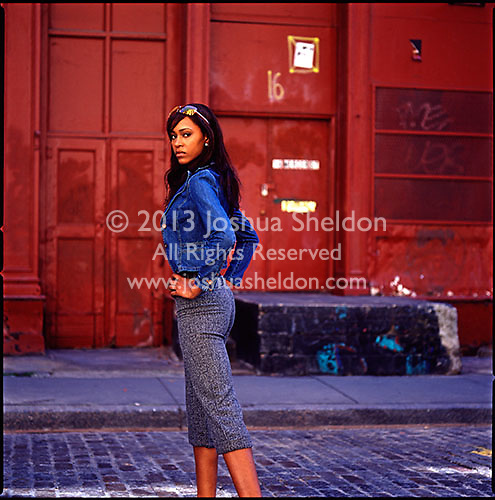 African American girl posing in front of burgandy colored building<br />