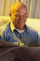 Retired man relaxing reading newspaper