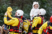 Pictured: Two firemen bring two young children to safety after being evacuated in Nantgarw, Wales, UK. Sunday 16 February 2020<br /> Re: Residents from Oxford Street in the village of Nantgarw had to be evacuated in inflatable boats by the Fire Service after rover Taff burst its banks in south Wales, UK.