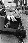 Young boy warming his hands from the heat from a hot Chestnut stall burner. The proprietor is talking to the Hot Dogs and Hamburgers van owner.  Stamford bridge Chelsea Football club while game is in progress. London England 1970