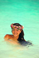 Young local girl swimming in the ocean with haku lei on