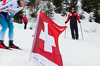 Switzerland. Canton Ticino. Swiss-Cups Campra. Cross Country Skiing. FIS Classic Sprint Race. Hippolyt Kempf  (R) is the Cross Country Skiing Chef by Swiss-Ski. He stands in the snow holding two ski poles and watches the race. Hippolyt Kempf (born 10 December 1965) is a Swiss Nordic combined skier who competed during the late 1980s and early 1990s. He won a complete set of Olympic medals, earning two of them at the 1988 Winter Olympics in Calgary (gold: 15 km individual, silver: 3 x 10 km team) and the third at the 1994 Winter Olympics in Lillehammer (bronze: 3 x 10 km team). Kempf also earned a 3 x 10 km team silver medal at the 1989 FIS Nordic World Ski Championships in Lahti. A Swiss competitor schusses down the mountain. Athletes are trained to achieve endurance, strength, speed, skill and flexibility at different levels of intensity. A swiss flag used by Swiss-Ski as symbol of its belonging to Switzerland. Swiss-Ski is a branch of Swiss Olympic. The Fédération Internationale de Ski (FIS; English: International Ski Federation) is the world's highest governing body for international winter sports. Founded  on 2 February 1924, it is responsible for the Olympic disciplines of cross-country skiing. The FIS is also responsible for setting the international competition rules. 4.01.2020 © 2020 Didier Ruef
