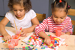 Preschool children ages 3-4 art activity two girls gluing shapes to paper and painting both using right hands to move shapes horizontal