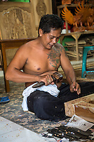 Bali, Indonesia.  Woodcarver Carving Design into Window Frame in Woodworker's Workshop.