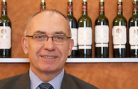 Alain Brumont, owner and winemaker at Chateau Montus and Domaine de Bouscasse Bouscassé. Madiran, France. Bottles of Bouscasse and Montus in the background Madiran France