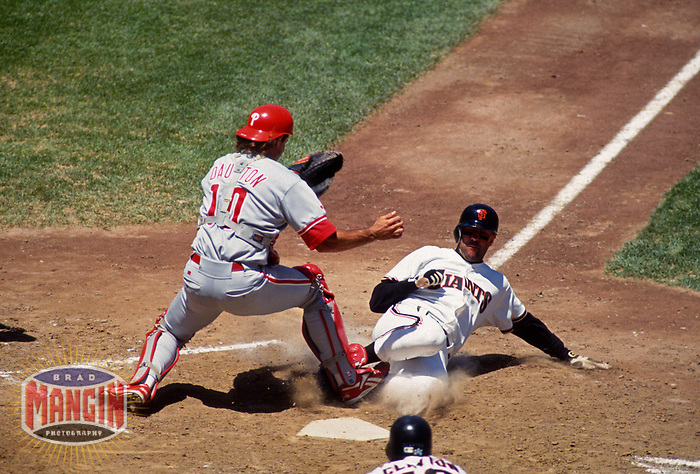 SAN FRANCISCO, CA:  Will Clark of the San Francisco Giants slides home safely as Philadelphia Phillies catcher Darren Daulton applies a late tag at Candlestick Park in San Francisco, California on Sunday July 25, 1993. (Photo by Brad Mangin)