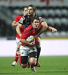 Andrew Bishop tackles Ian Keatley..RaboDirect Pro12.Ospreys v Munster.Liberty Stadium.03.12.11.©Steve Pope