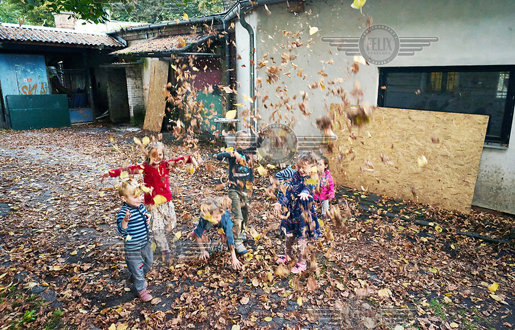 Children playing with autumn leaves.