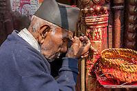 Nepal, Kathmandu.  Hindu Man Applying a Tika of Kumkuma Powder to his Forehead before Praying at the Ashok Binayak (Maru Ganesh) Temple, Durbar Square.