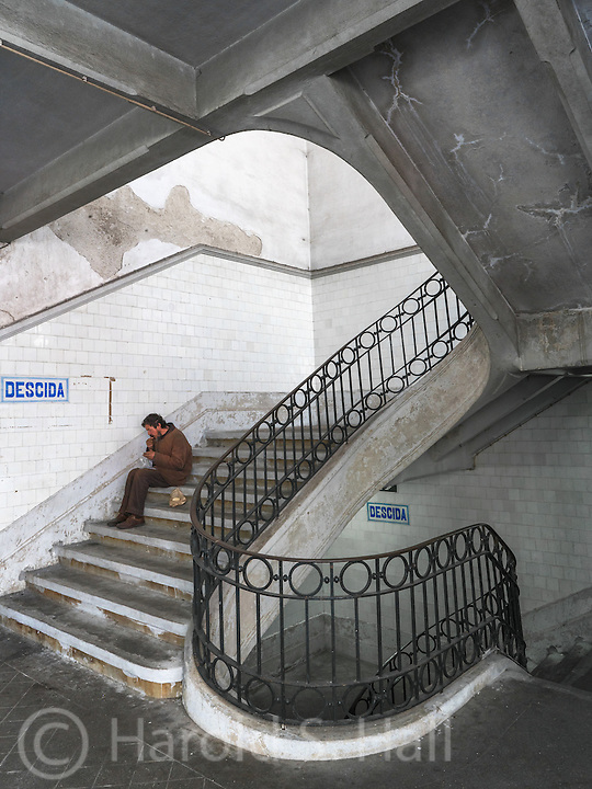 The stairs descending to the well known and permanant farmer's market in Porto, Portugal.  The man eating on the stairs seemed to fit the description, descending.
