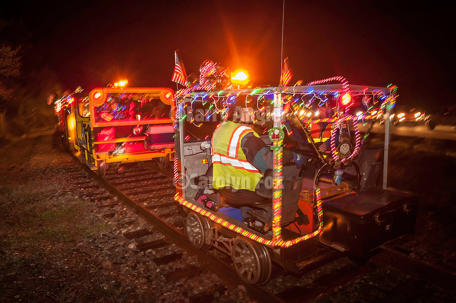 Annual Christmas run on the Amador Central Railroad rail motorcars lit with festive lights on a journery from Ione to Martel in the evening, Amador County, Calif.