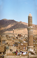 Woman hanging out washing beneath a minaret in the Old City of Sana'a, one of the most ancient towns in the Arab world, established on an important trading route over two thousand years ago.