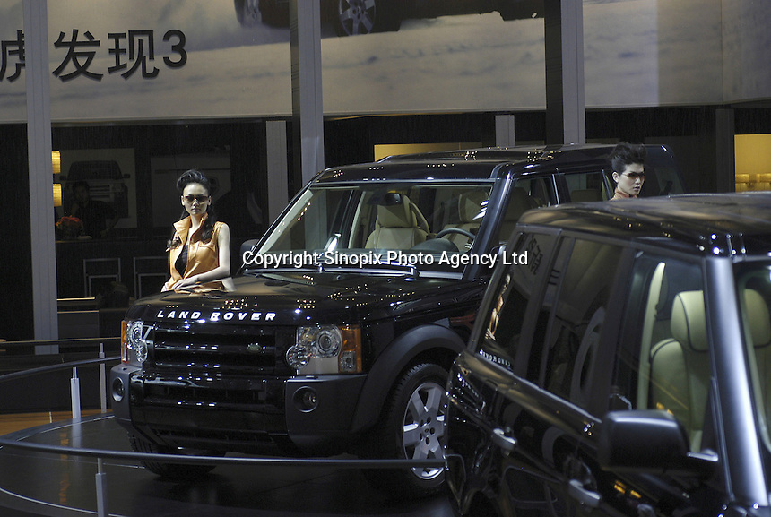 Chinese models pose besides Land Rover at the Auto China 2004 exhibition in Beijing, China. MG Rover & Shanghai Automotive Industry Corporation announce co-operation agreement, SAIC becomes MG Rover's new joint venture partner..