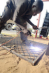 A welder constructs a metal door at his street front shop in Likoni, Kenya.
