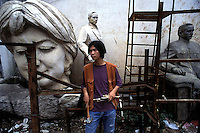 A young sculptor stands in front of his sculptures.