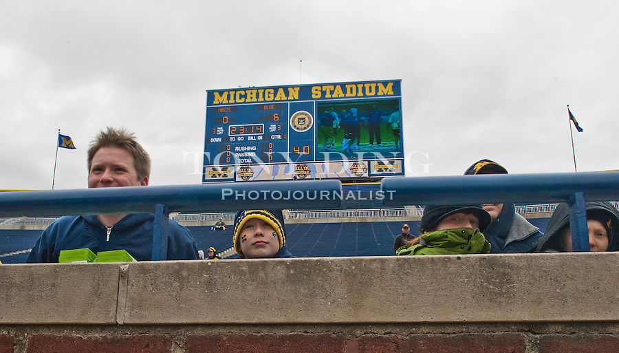 Michigan fans huddled under blankets and bundled layers to brave the freezing wind chill to attend the Wolverines' spring football game, Saturday, April 17, 2010, in Ann Arbor, Mich. The University announced approximately 35,000 showed up. (AP Photo/Tony Ding)