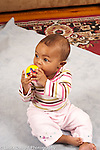 7 month old baby girl  sitting full length holding toy ball vertical