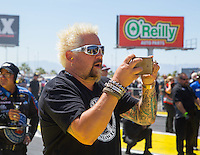 Apr 12, 2015; Las Vegas, NV, USA; Celebrity chef Guy Fiere reacts as he watches NHRA top fuel driver Shawn Langdon during the Summitracing.com Nationals at The Strip at Las Vegas Motor Speedway. Mandatory Credit: Mark J. Rebilas-