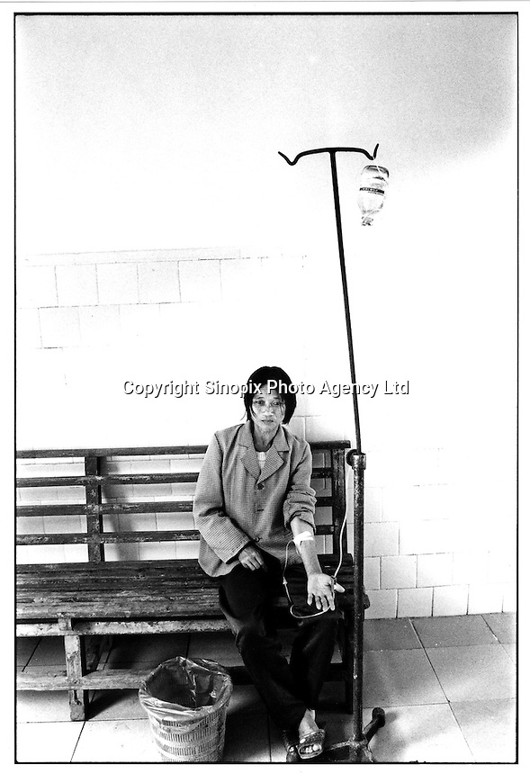 A lady sits on a wooden bench in the local village hospital in Huaji county, Guangdong Province, China. The cost for fees at the spartan hospital are around 30 RMB per day which is far too expensive for most villagers who use quack doctors. China spends just 20% of it's health care budget in the rural area despite these areas having 70% of the 1.3 billion population. The poverty gap in China is a major theme at this years National People's Congress in Beijing since it is causing destabilization of the country...PHOTO BY SINOPIX.