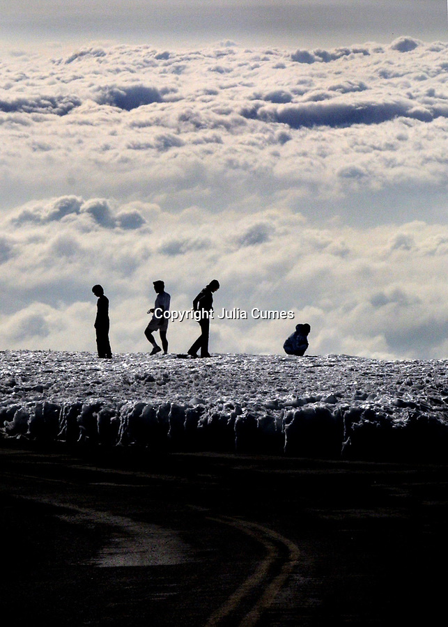 Visitors enjoy the snow and view of the clouds almost 14,000 feet high on the top of Mauna Kea on the Big Island of Hawaii.