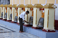 Myanmar, Burma.  Mandalay.  Worshiper Strikes one of the Mahamuni Buddhist Temple Bells.  This is done to announce one's arrival, summoning good spirits and driving away evil ones.