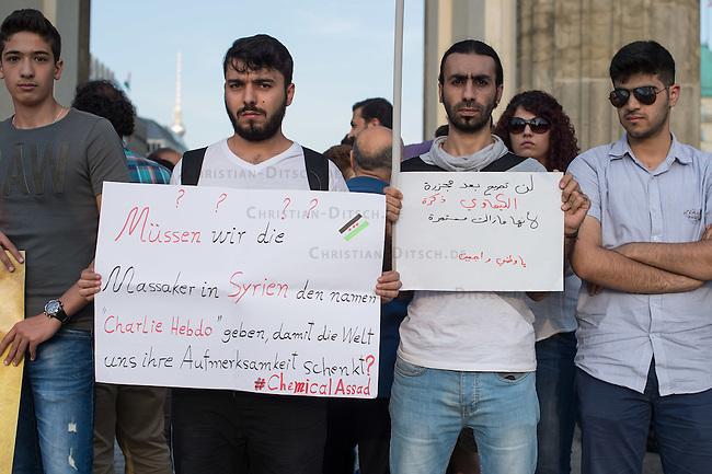 """Protest gegen den syrischen Diktator Bashar al-Assad.<br /> Am Freitag den 21. August 2015 protestierten mehrere hundert Menschen, die meissten Buergerkriegsfluechtlinge aus Syrien, gegen den fortdauernden Buergerkrieg in ihrem Herkunftsland. Sie gedachten annlaesslich des 2. Jahrestag der Opfer des Giftgas-Angriffs vom 21. August 2013 in Damaskus. Das Assad-Regime hatte ueber 1.600 Menschen mit dem Nervengift Sarin ermordet.<br /> Nach Angaben des deutschen Vertreters der """"Syrischen Nationalen Koalition"""", Dr Bassam Abdullah,  werden in Syrien weiterhin Menschen durch Giftgas durch die Regierungstruppen getoetet. Die Koalition ist ein Zusammenschluss von syrischen Muslimen, Christen, Assyrern und Kurden.<br /> Im Bild: Ein Demonstrant haelt ein Plakat auf dem er fragt: """"Muessen wir die Massaker in Syrien den Namen 'Charlie Hebdo' geben, damit die Welt uns ihre Aufmerksamkeit schenkt? #ChemicalAssad"""".<br /> 21.8.2015, Berlin<br /> Copyright: Christian-Ditsch.de<br /> [Inhaltsveraendernde Manipulation des Fotos nur nach ausdruecklicher Genehmigung des Fotografen. Vereinbarungen ueber Abtretung von Persoenlichkeitsrechten/Model Release der abgebildeten Person/Personen liegen nicht vor. NO MODEL RELEASE! Nur fuer Redaktionelle Zwecke. Don't publish without copyright Christian-Ditsch.de, Veroeffentlichung nur mit Fotografennennung, sowie gegen Honorar, MwSt. und Beleg. Konto: I N G - D i B a, IBAN DE58500105175400192269, BIC INGDDEFFXXX, Kontakt: post@christian-ditsch.de<br /> Bei der Bearbeitung der Dateiinformationen darf die Urheberkennzeichnung in den EXIF- und  IPTC-Daten nicht entfernt werden, diese sind in digitalen Medien nach §95c UrhG rechtlich geschuetzt. Der Urhebervermerk wird gemaess §13 UrhG verlangt.]"""