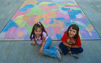Two girls pose with their driveway chalk art