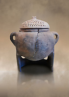Hittite terra cotta cooking pot with perforated lid on a charcoal burner pot stand. Hittite Empire, Alaca Hoyuk, 1450 - 1200 BC. Çorum Archaeological Museum, Corum, Turkey. Against a warm art bacground.