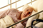 elderly man lying in hospital bed with worrying, dazed look