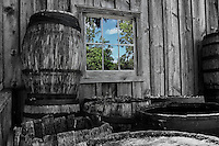 Old black and white whiskey barrels are around the window reflection of a new colourful day in Black Creek Pioneer Village in Toronto.