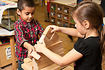 Education Preschool 3-4 year olds boy and girl building construction with wooden blocks together
