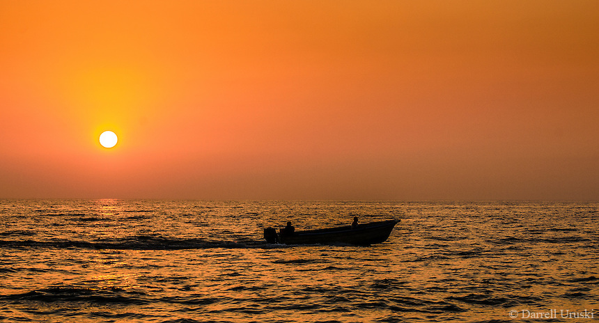Fine Art Landscape Photograph. Sunset scene of a fishing against a golden glowing sky.