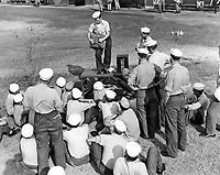 Students receiving familiarization with flight photography at Chevalier Field.  Instructor J. L. Estano PhoM 1/c,  giving instructions in the parachute to photo students awaiting flight at North Line.