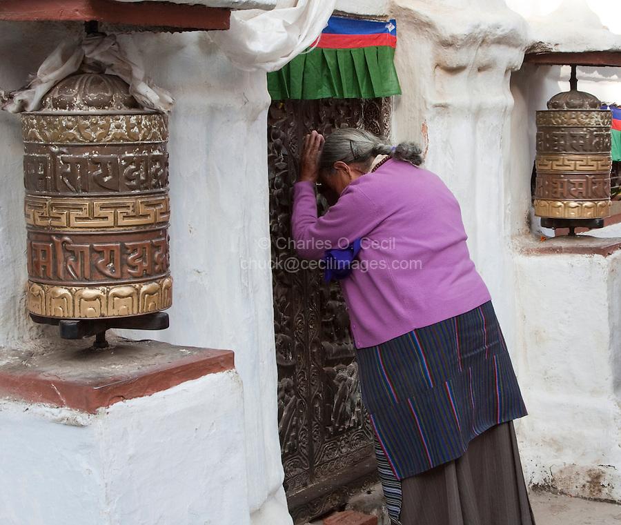 Bodhnath, Nepal.  Buddhist Worshiper Praying at Entrance to Stupa, Prayer Wheels on Left and Right.