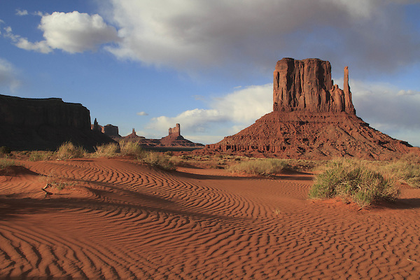 The Mitten rock formation and sand dunes in Monument Valley Navajo Tribal Park, Arizona, USA. . John offers private photo tours in Monument Valley and throughout Arizona, Utah and Colorado. Year-round.