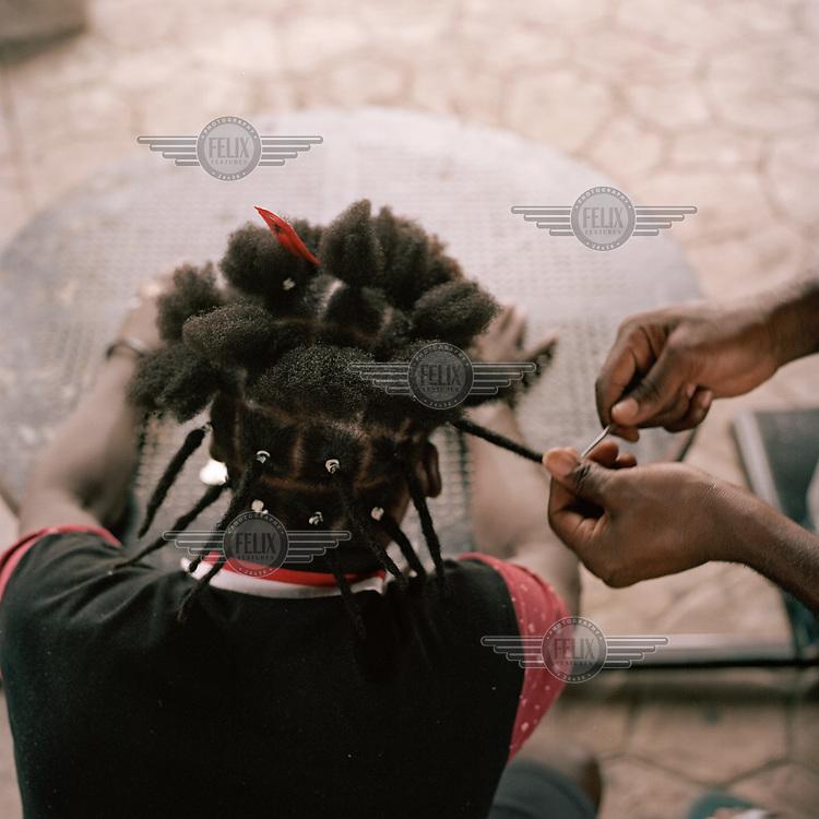 Two Haitian migrants twist each other's hair into plaits (braids) while spending time in a city park. Following pressure in July 2019 from the US government the Mexican authorities stopped issuing  transit visas to migrants and asylum seekers hoping to cross into the USA leaving large numbers stuck in the city.