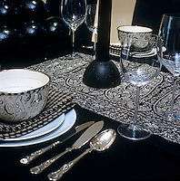 Detail of a place setting laid with black and white linen and tableware on a black dining table