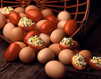 egg salad filled tomatoes shown with eggs in shell