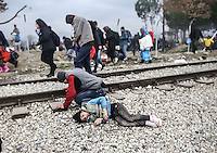 Pictured: Two refugees fall on the ground Monday 29 February 2016<br /> Re: A crowd of migrants has burst through a barbed-wire fence on the FYRO Macedonia-Greece border using a steel pole as a battering ram.<br /> TV footage showed migrants pushing against the fence at Idomeni, ripping away barbed wire, as FYRO Macedonian police let off tear gas to force them away.<br /> A section of fence was smashed open with the battering ram. It is not clear how many migrants got through.<br /> Many of those trying to reach northern Europe are Syrian and Iraqi refugees.<br /> About 6,500 people are stuck on the Greek side of the border, as FYRO Macedonia is letting very few in. Many have been camping in squalid conditions for a week or more, with little food or medical help.