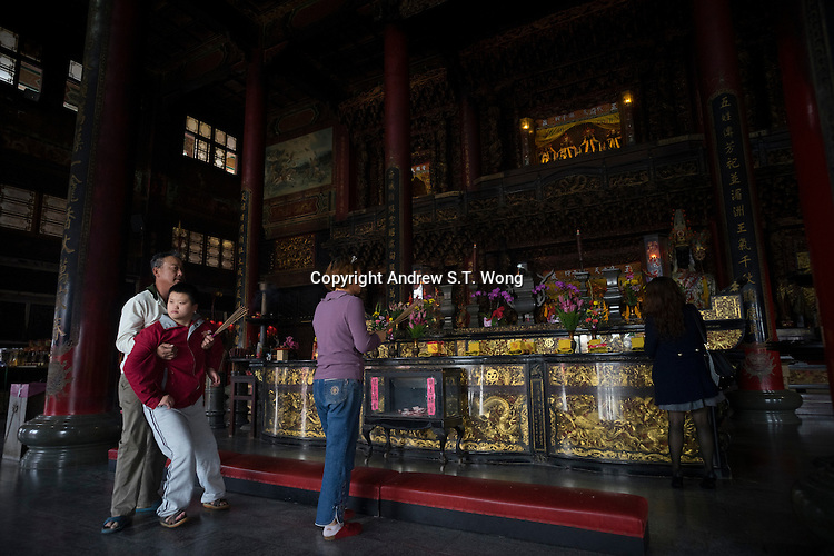 Taiwanese parents with their son suffering from mental illness pray at the Orthodox Luerhmen Shen Mu Temple in Tainan, Taiwan, 2015. The temple worships Matsu who is the most famous sea goddess in the Chinese world.