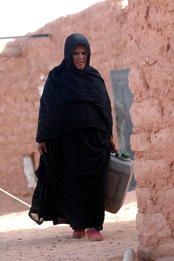 A woman carries water on December 12, 2003, in the Saharawi refugee camps. Saharawi people have been living at the refugee camps of the Algerian desert named Hamada, or desert of the deserts, for more than 30 years now. Saharawi people have suffered the consecuences of European colonialism and the war against occupation by Moroccan forces. Polisario and Moroccan Army are in conflict since 1975 when Hassan II, Moroccan King in 1975, sent more than 250.000 civilians and soldiers to colonize the Western Sahara when Spain left the country. Since 1991 they are in a peace process without any outcome so far. (Ander Gillenea / Bostok Photo)
