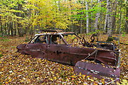 Old four door Chevrolet car surrounded by leaf drop at the abandoned site of the old North Woodstock Civilian Conservation Corps Camp in North Woodstock, New Hampshire.
