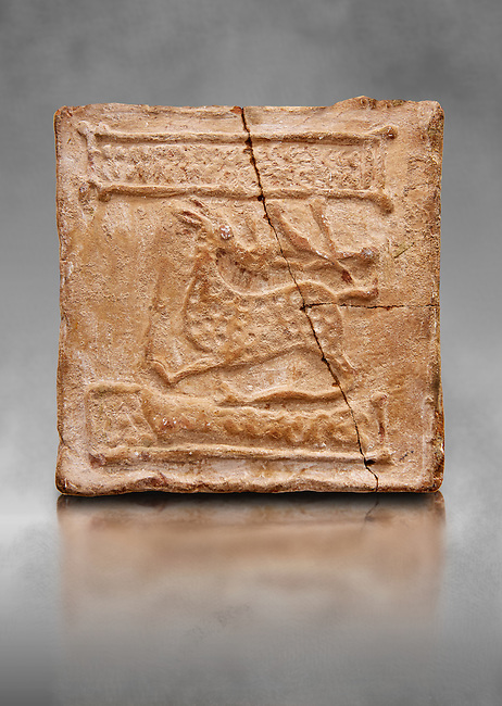 6th-7th Century Eastern Roman Byzantine  Christian Terracotta tiles depicting a stag - Produced in Byzacena -  present day Tunisia. <br /> <br /> The stag is a traditional Christian symbol for Christ, Who tramples and destroys the Devil. In the Medieval bestiaries the stag as an enemy of snakes. It was believed that stags was believed to chase snakes into their holes or rock crevices, driving them out by flooding the hole with the breath or water from its mouth, and eating them. <br /> <br /> These early Christian terracotta tiles were mass produced thanks to moulds. Their quadrangular, square or rectangular shape as well as the standardised sizes in use in the different regions were determined by their architectonic function and were designed to facilitate their assembly according to various combinations to decorate large flat surfaces of walls or ceilings. <br /> <br /> Byzacena stood out for its use of biblical and hagiographic themes and a richer variety of animals, birds and roses. Some deer and lions were obviously inspired from Zeugitana prototypes attesting to the pre-existence of this province's production with respect to that of Byzacena. The rules governing this art are similar to those that applied to late Roman and Christian art with, in the case of Byzacena, an obvious popular connotation. Its distinguishing features are flatness, a predilection for symmetrical compositions, frontal and lateral representations, the absence of tridimensional attitudes and the naivety of some details (large eyes, pointed chins). Mass production enabled this type of decoration to be widely used at little cost and it played a role as ideograms and for teaching catechism through pictures. Painting, now often faded, enhanced motifs in relief or enriched them with additional details to break their repetitive monotony.<br /> <br /> The Bardo National Museum Tunis, Tunisia. Against a grey art background.