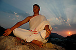 A student of Om Shantidhama meditating during sunset. Om Shantidhama is a residential vedic school for boys. Nestled among the confluence of hills, forest and rivers - Om Shanti Dhama is a world removed from the maddeningly fast and often chaotic urban India. Students from allover the country are selected to take part in its Vedic and free education system. What is unique about this institute is that they have blended the traditional and modern education system. Here computer and science is taught with the same passion as the Vedas and Shastras, helping the students to grow spiritually as well as earn a living. Bonding with the nature and animal world is a mandatory part of the institute's curriculum. Karnataka, India. Arindam Mukherjee